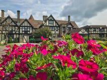 Tudorstilvilla mit rosa Blumen im Vordergrund Lizenzfreie Stockfotografie