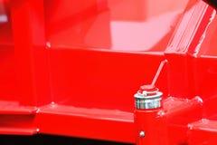Tuerca de tornillo en la maquinaria industrial del detalle rojo de la placa de acero Foto de archivo