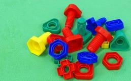 Tuercas coloridas del juguete - y - tornillos fotos de archivo