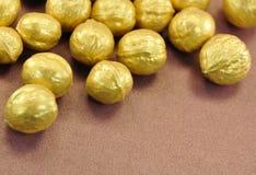 Tuercas de oro en el fondo de Brown Foto de archivo libre de regalías