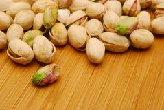 Tuercas de pistacho en tarjeta de madera Fotografía de archivo