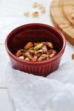 Tuercas de pistacho en taza roja Imagen de archivo libre de regalías