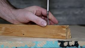 Tuerza el tornillo en un bloque de madera metrajes