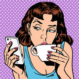 Tuesday girl looks at smartphone drinking tea or Stock Image