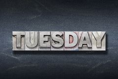 Tuesday word den. Tuesday word made from metallic letterpress on dark jeans background Royalty Free Stock Image