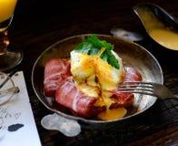 Tueste con el tocino y el huevo escalfado en un sartén, bifurcación del vintage en un fondo oscuro Fotos de archivo