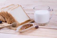 Tueste el pan del trigo cortado y la leche de vaca con el panal en de madera, fotografía de archivo libre de regalías