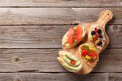 Tueste los bocadillos con el aguacate, tomates, salmones Foto de archivo libre de regalías