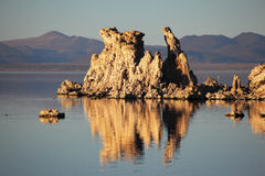 Tufa stalactites are reflected in smooth water Royalty Free Stock Images