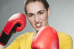 Tuff fighting lady wearing boxing gloves. Conflicting young woman defending herself with boxing gloves for competition concept royalty free stock images