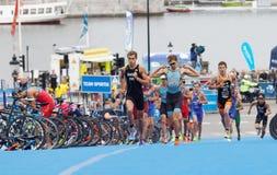 Tuff kamp mellan rinnande triathletes Arkivbilder