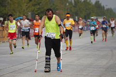 Tuff man Racing med benbrott i maraton Royaltyfri Foto
