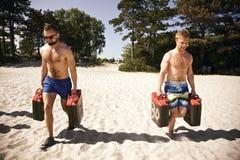 Tuffa idrottsman nen som gör genomkörare på stranden med bensindunkar Arkivfoto