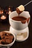 Tuffandosi nella fonduta di cioccolato Immagini Stock
