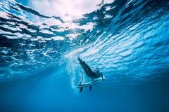 Tuffo attraente della donna del surfista subacqueo con sotto l'onda in oceano immagini stock libere da diritti