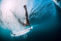 Tuffo della donna del surfista subacqueo con le onde di sotto fotografia stock