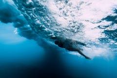 Tuffo della donna del surfista subacqueo Tuffo di Surfgirl sotto l'onda fotografie stock libere da diritti