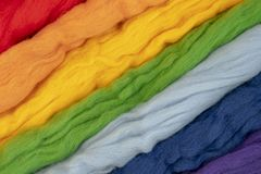 Tufts of wool of different colors parallel to each other form a rainbow. Conceptual photo.  stock photos