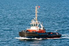 The tug AROS navigates on the sea to assist a cruise ship entering the port stock photography
