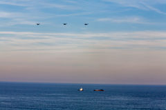 Tug and barge in the Atlantic Ocean. A tug boat and barge with 3 military helicopters overhead Royalty Free Stock Image