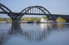 Tug with barge passes under the road bridge. Rybinsk Stock Photography