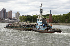 Tug and barge of scrap metal on East River NYC Stock Images