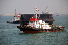 Tug and barge in Singapore anchorage. A small tug seen towing a large barge in Singapore anchorage Stock Images