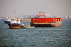 Tug and barge in Singapore anchorage. A small tug seen towing a large barge in Singapore anchorage Royalty Free Stock Photo