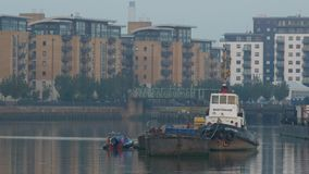 Tug and barges on the Thames at dawn. stock video