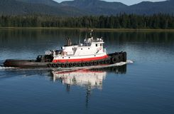 Tug Boat in Alaska. A tug boat underway in calm Alaska waters stock images