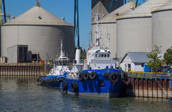 Tug boat on coast. Tug boat on Sorel-Tracy, Qc, Canada port in front of grain silos at daytime summer Royalty Free Stock Photos