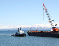 Tug boat and crane. A tug boat pulling into an industrial shipping yard with a crane in Alaska with a bright blue sky Stock Photo
