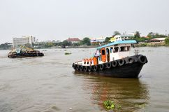 Tug boat drags sand barge on Chao Phraya river, Bangkok Royalty Free Stock Image