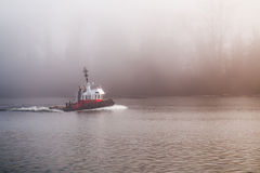 Tug Boat on a foggy day. A tug boat motors down a river on a cold and foggy day Royalty Free Stock Image
