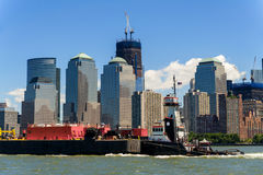 Tug Boat and Freighter head north along the Hudson in front of t. A tugboat pushes a freighter up along the Hudson River as Lower Manhattan's World Trade Center Royalty Free Stock Photo