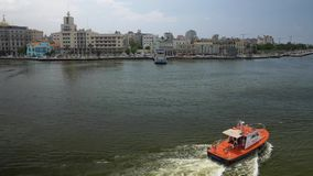 Tug Boat in Havana Port Bay with City Skyline in Background. A small tug pilot boat travels in Havana Port Bay with the old town skyline in the distance stock footage