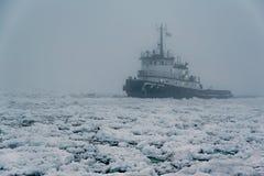 A tug boat navigating Lake Michigan. In the winter Royalty Free Stock Photography