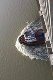 A Tug Boat Passes Beneath a Bridge Stock Image