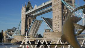 Tug boat passes under Tower Bridge. On a sunny autumn morning. Framed by the statue of girl with dolphin and shot in 4K stock video footage