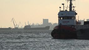 Tug Boat at the pier. On the roads freighter overload. stock footage