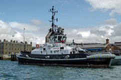 Tug Boat, Portsmouth Dockyard. PORTSMOUTH, ENGLAND - AUGUST 2: A private tug boat operated by the company Serco at work for the Royal Navy in the dockyard at Stock Photos