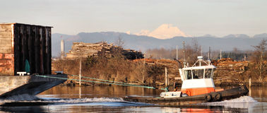 Tug boat pulling cargo. A tug boat passing down the river pulling a large barge with mount baker in the background royalty free stock photography