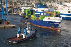 Tug boat pulling cargo ship carrying containers to sea at Port of Civitavecchia, Italy, the Port of Rome Stock Photography