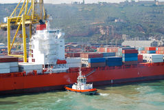 Tug Boat aligns container ship Barcelona Spain Royalty Free Stock Photo