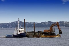 Tug boat pushing dredging barge Stock Photo
