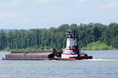 Tugboat Pushing a Heavy Barge Royalty Free Stock Image