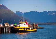 Tug Boat at Rest. View of yellow tug boat tied up at docks in Valdez, Ak Royalty Free Stock Photos