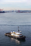 Tug boat in Seattle. Tug boat in Elliot Bay with Port of Seattle in the background Royalty Free Stock Image