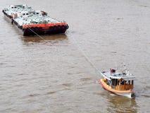 Tug boat service on CHAO  PHRAYA river BANGKOK, THAILAND pulling heavy floating container Stock Photos