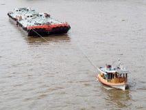 Tug boat service on CHAO  PHRAYA river BANGKOK, THAILAND pulling heavy floating container Royalty Free Stock Photo